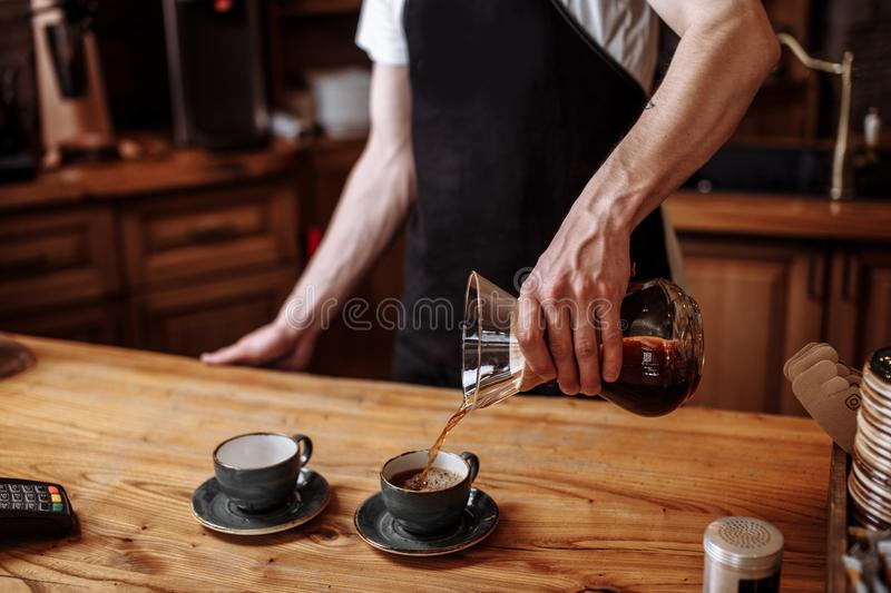 Waiter is pouring ground coffee in the cups for visitors. A waiter is pouring ground coffee in the cups for visitors stock photography