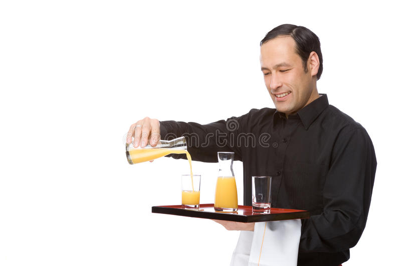 Waiter pouring juice stock photography