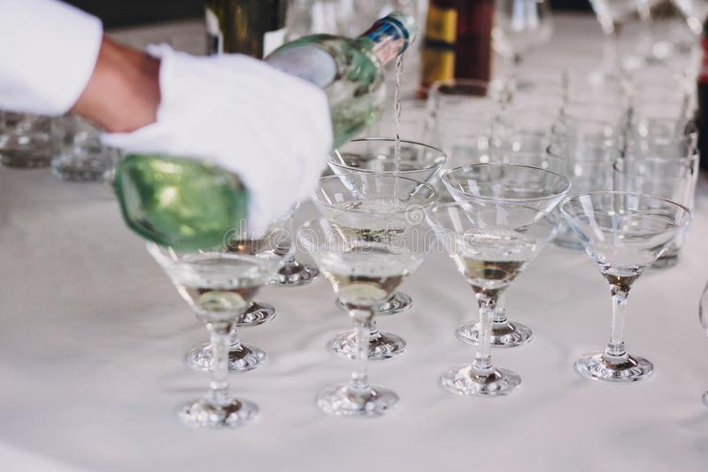 Waiter pouring martini in crystal glasses on table party at wedding reception. Martini row drinks at alcohol bar. Christmas and royalty free stock photo
