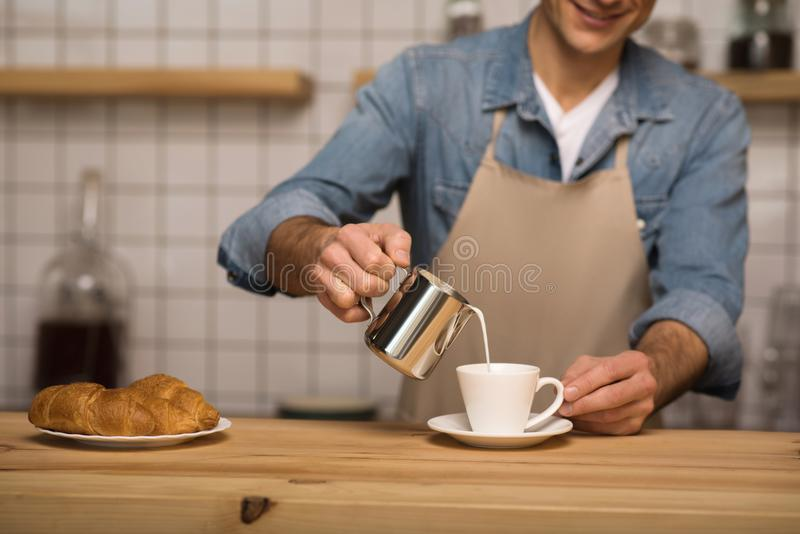 Waiter pouring milk into coffee. Smiling young waiter pouring milk into coffee stock images