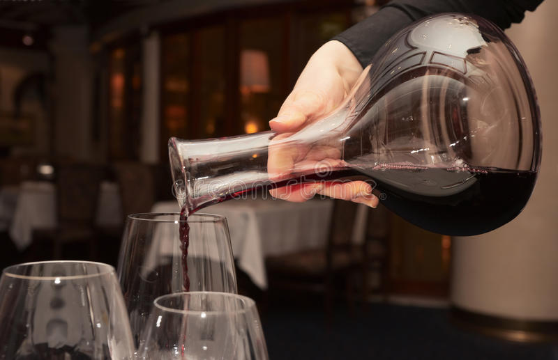 Waiter pouring red wine from decanter. In dark restaurant royalty free stock photography