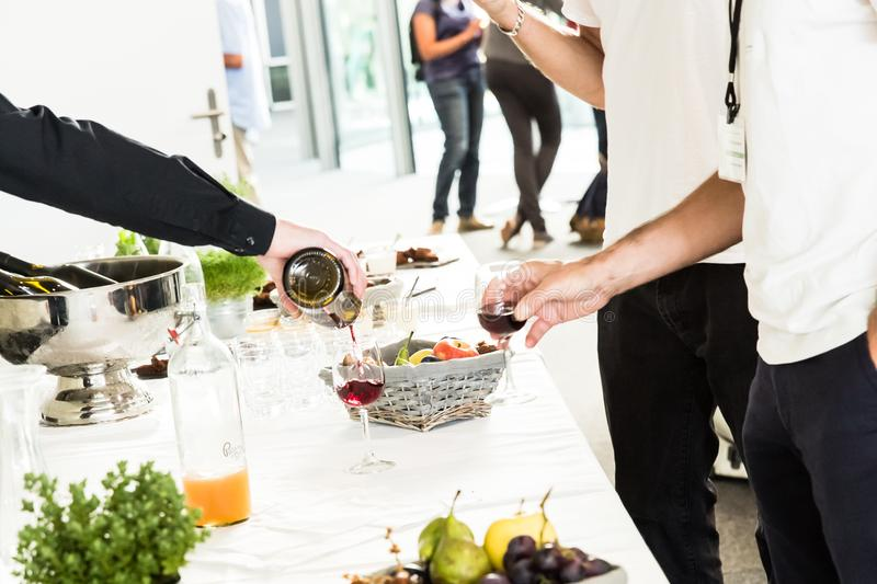 Waiter Pouring Red Wine Glass to Two Men on White Buffet Table stock photo