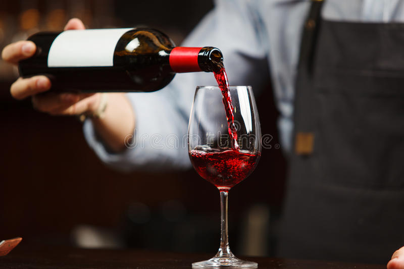 Waiter pouring red wine into wineglass. Sommelier pours alcoholic drink royalty free stock images