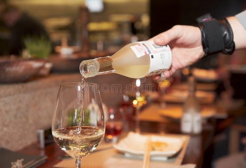 Waiter pouring saki stock images