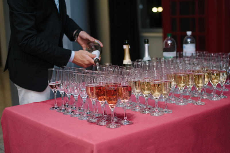 waiter pours the champagne into glasses at the buffet table royalty free stock image