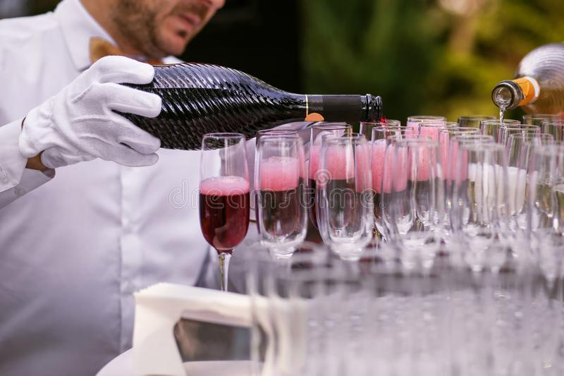 The waiter pours champagne into glasses for a party, red wine in glasses, champagne at a celebration.  stock photo