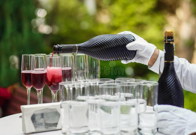 The waiter pours champagne into glasses for a party, red wine in glasses, champagne at a celebration.  stock images