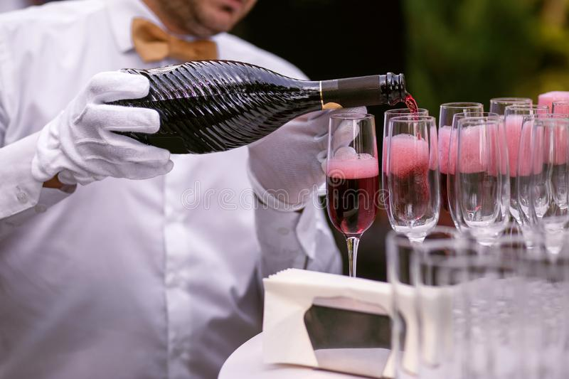 The waiter pours champagne into glasses for a party, red wine in glasses, champagne at a celebration.  royalty free stock image