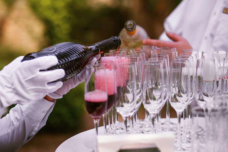 The waiter pours champagne into glasses for a party, red wine in glasses, champagne at a celebration.  royalty free stock photos
