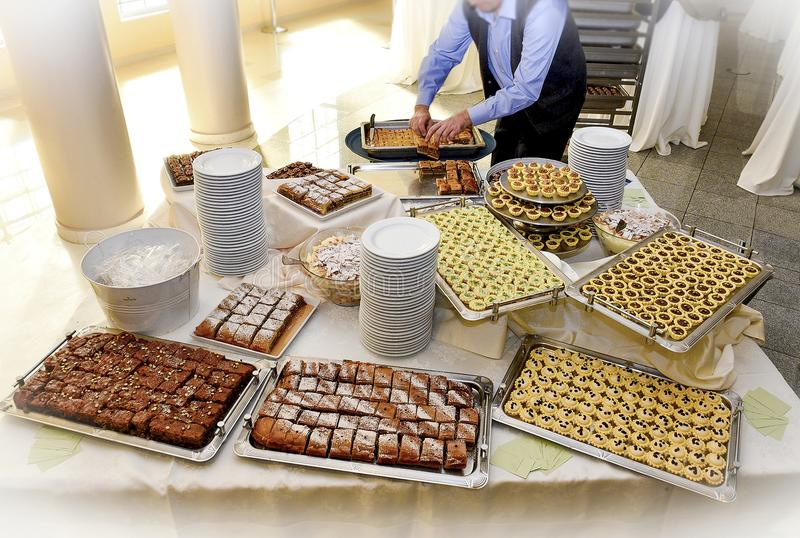Waiter prepares a table with gluten free sweets royalty free stock photos