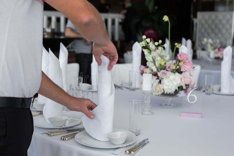 The waiter in the restaurant set up a table for guests. Waiter`s hands are a white tablecloth, napkins, white dishes and a bouque royalty free stock images