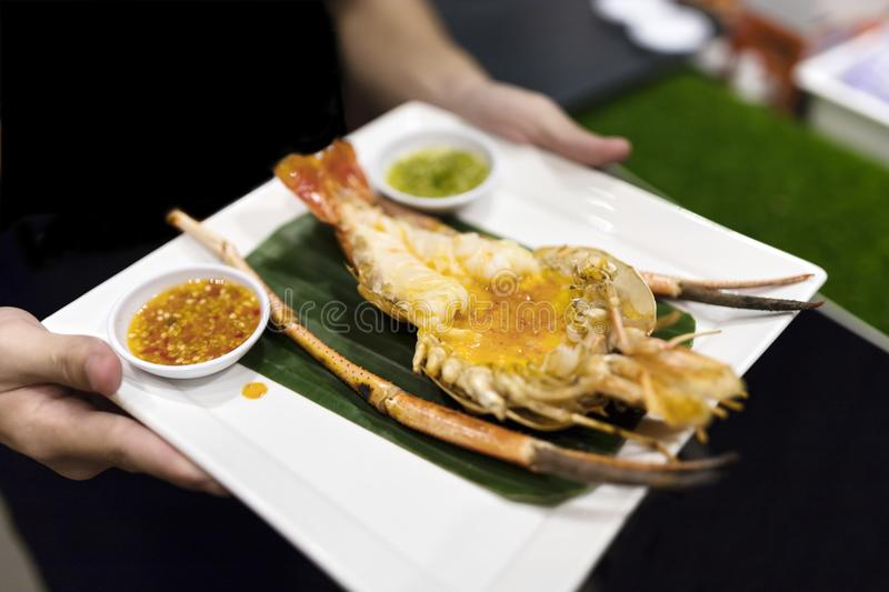 The waiter served a plate of grilled prawn on the banana leaf and Thai spicy sauce. royalty free stock photos