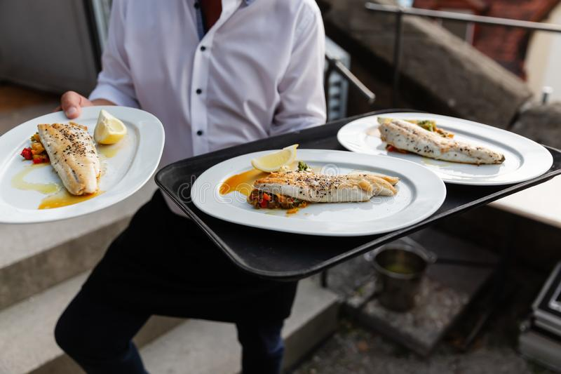 Waiter serves dishes with fish stock images