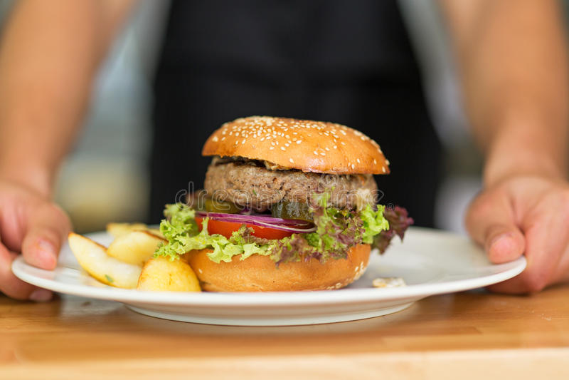 Waiter serves hamburger stock photo