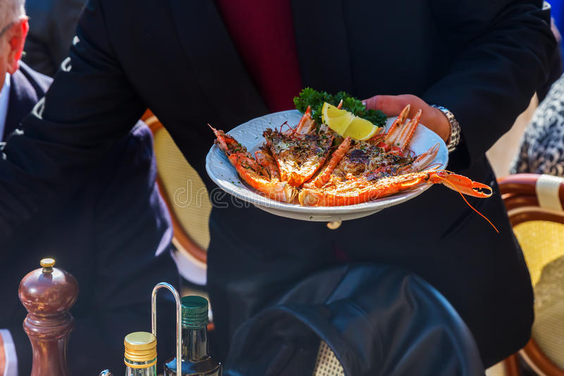 Waiter serves a plate with lobster stock photos