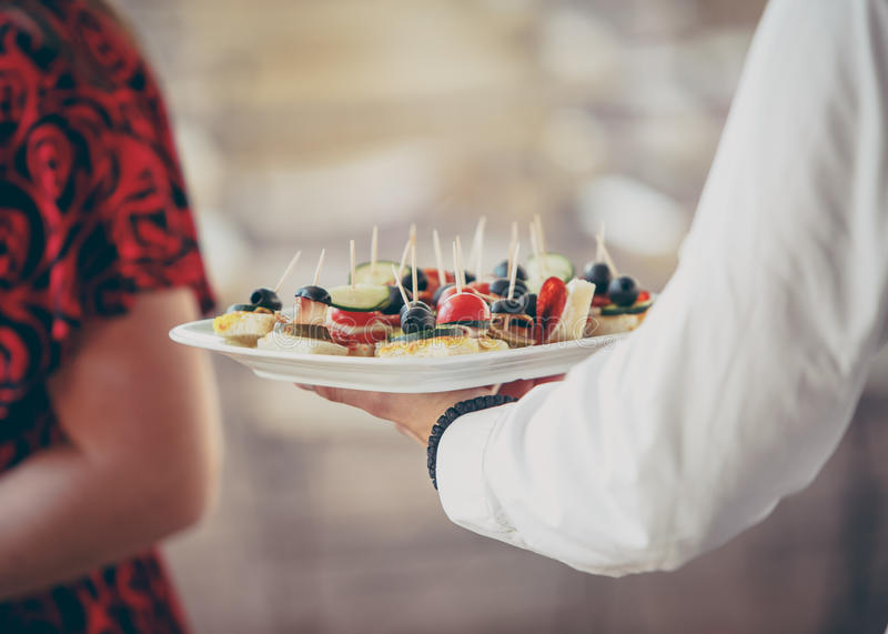 Waiter serving appetizers stock image