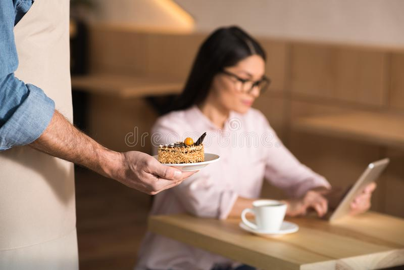 Waiter serving cake for businesswoman. Using digital tablet in cafe, focus on foreground royalty free stock image