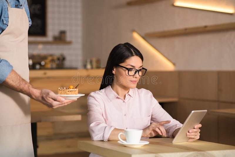 Waiter serving cake for businesswoman. Using digital tablet in cafe stock photography