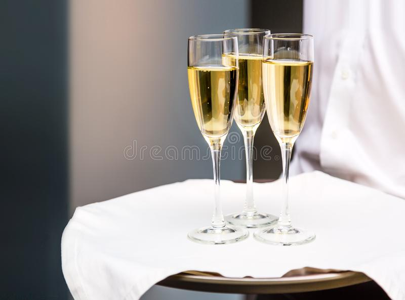 Waiter serving champagne glasses on a tray in a restaurant. Anniversary celebration concept stock photos