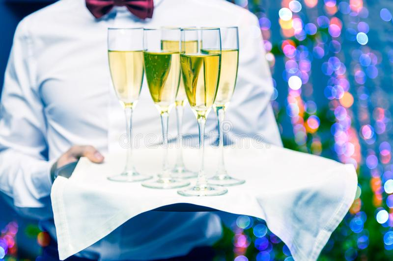 Waiter serving champagne glasses on a tray in a restaurant. Nice bokeh Christmas lights and Christmas tree in the background stock images