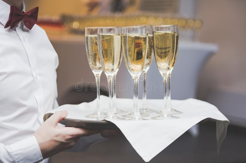 Waiter serving champagne glasses on a tray in a restaurant royalty free stock photography