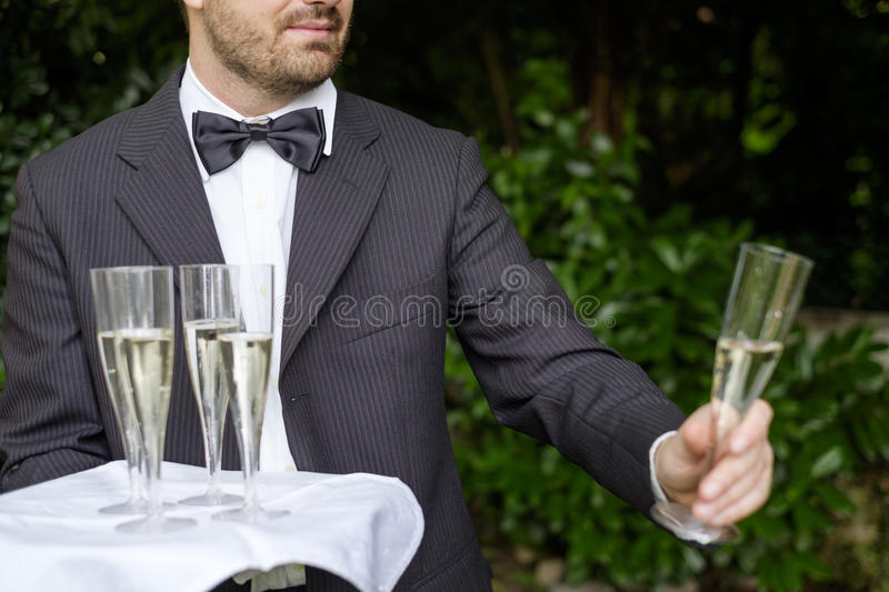 Waiter serving champagne glasses on a tray royalty free stock photos