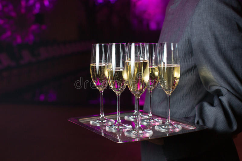 Waiter serving champagne on a tray stock photos