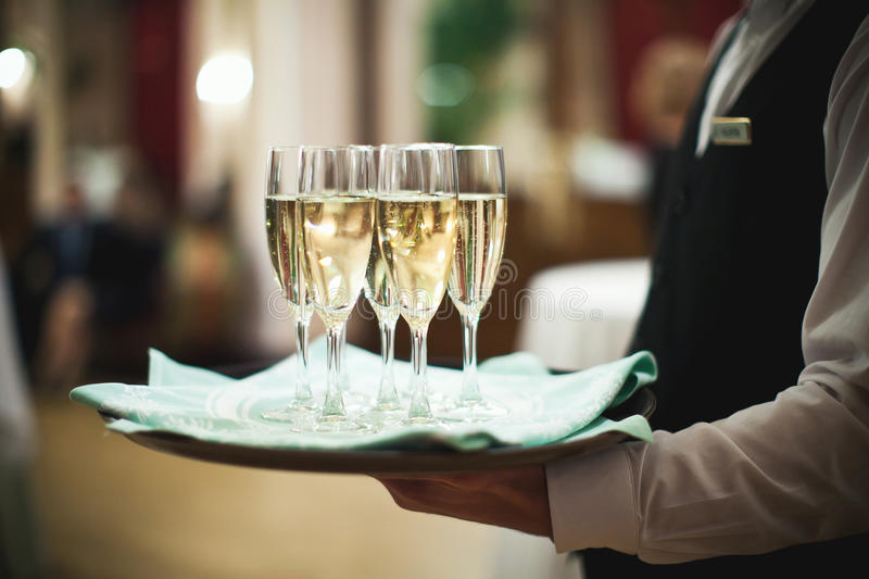 Waiter serving champagne on a tray at stock images