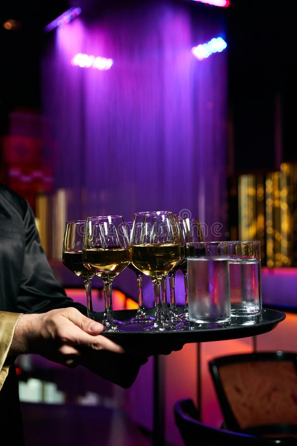 Waiter serving champagne and water on a tray stock photos