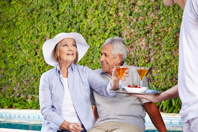 Waiter serving cocktails to senior people stock images