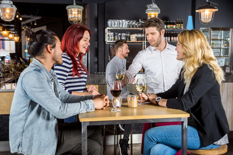 Waiter Serving Drinks To Customers In Bar. Young waiter serving drinks to customers at table in bar royalty free stock photography