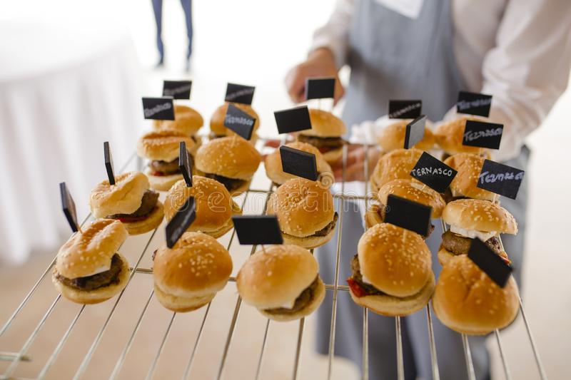 Waiter serving lamb burgers royalty free stock images