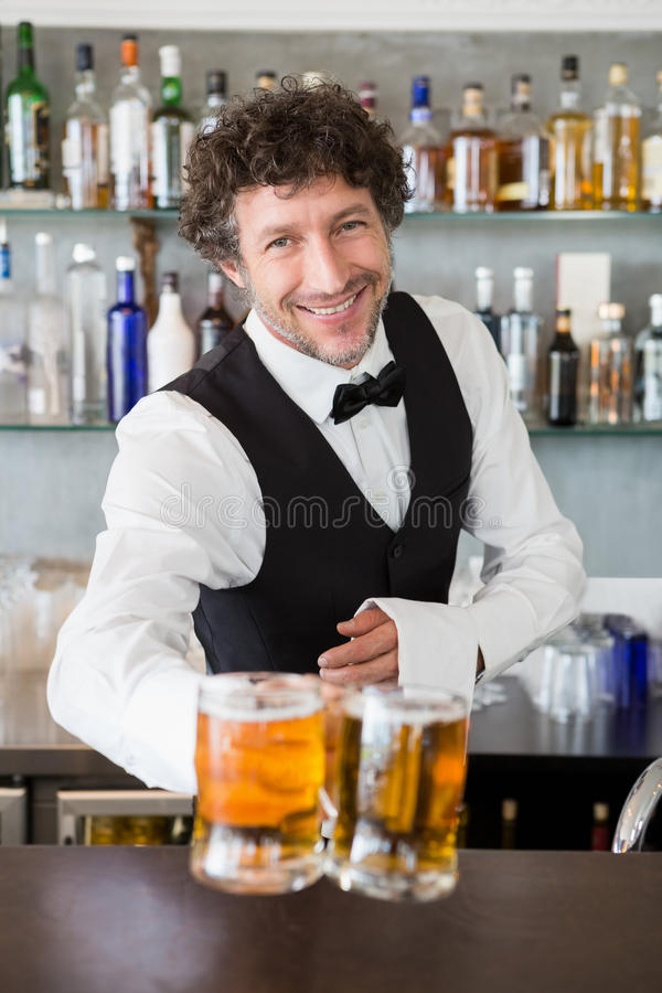 Waiter serving mug of beers stock photography