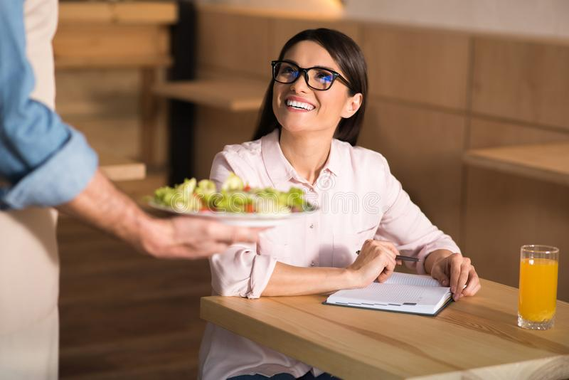 Waiter serving salad for businesswoman. Waiter serving salad for smiling businesswoman in cafe royalty free stock image