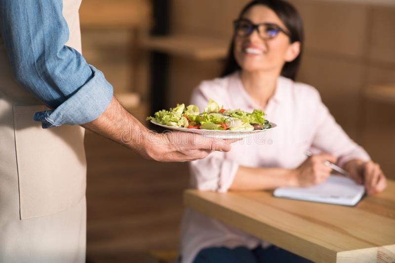 Waiter serving salad for businesswoman. Waiter serving salad for smiling businesswoman in cafe, focus on foreground stock image