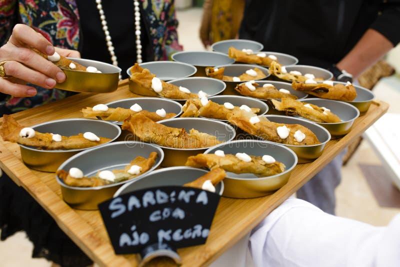 Waiter serving sardine appetizers with black garlic royalty free stock image