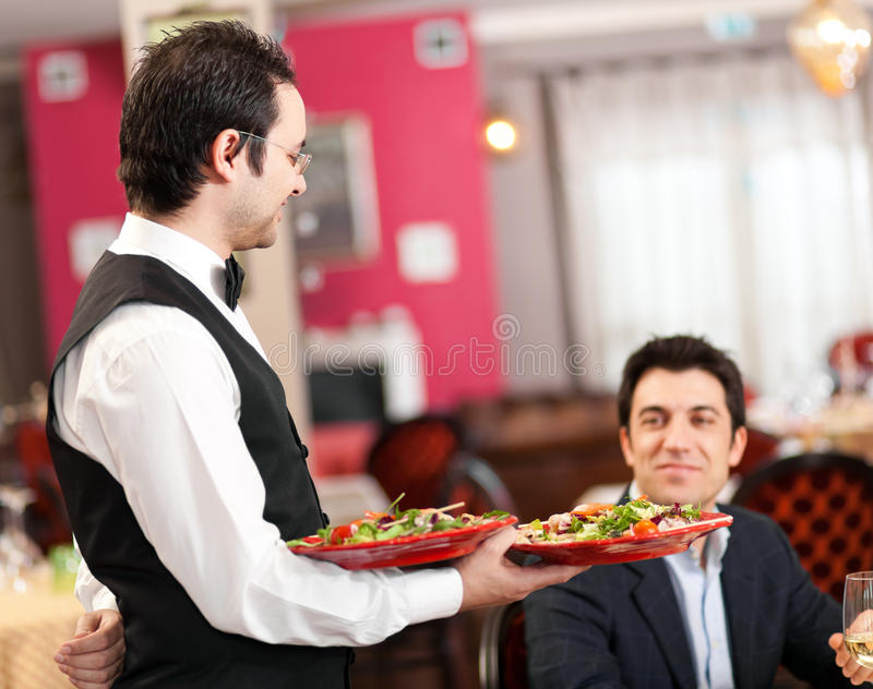 Waiter serving sea food stock photography