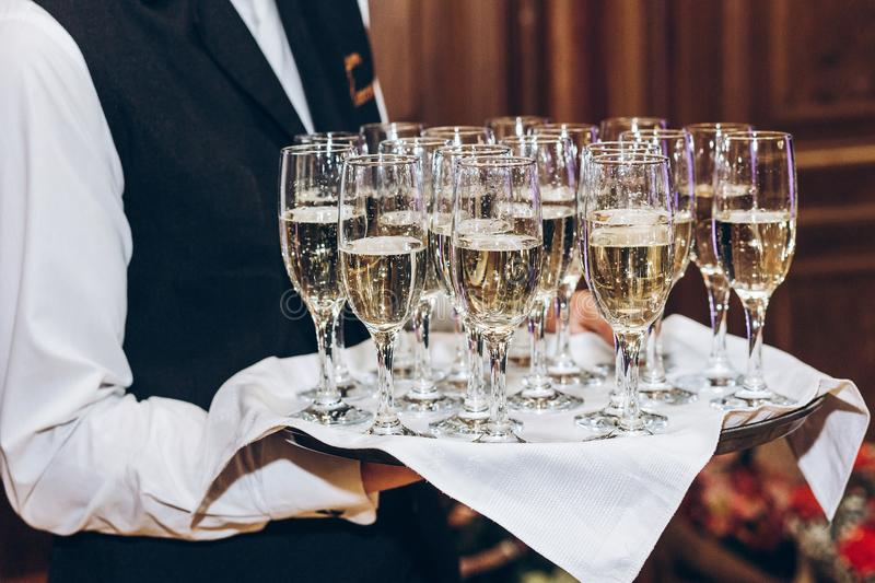 waiter serving stylish golden champagne in glasses on tray. elegant glasses of alcohol drinks serving at luxury wedding reception royalty free stock photos