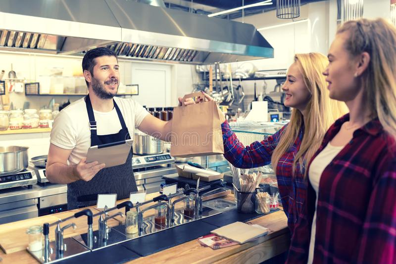 Waiter serving takeaway food to customers at counter in small family eatery restaurant royalty free stock photo