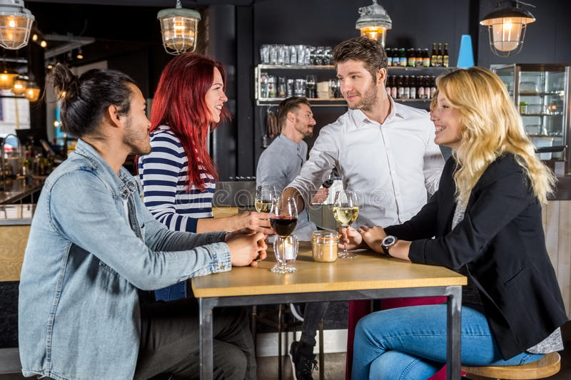 Waiter Serving Wine To Customers In Bar. Young waiter serving wine to customers at table in bar stock photo