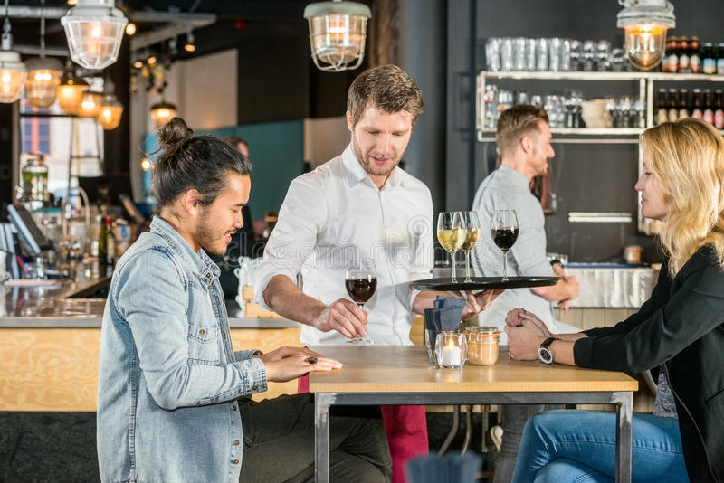 Waiter Serving Wine To Customers In Bar. Young waiter serving wine to customers at table in bar royalty free stock photography