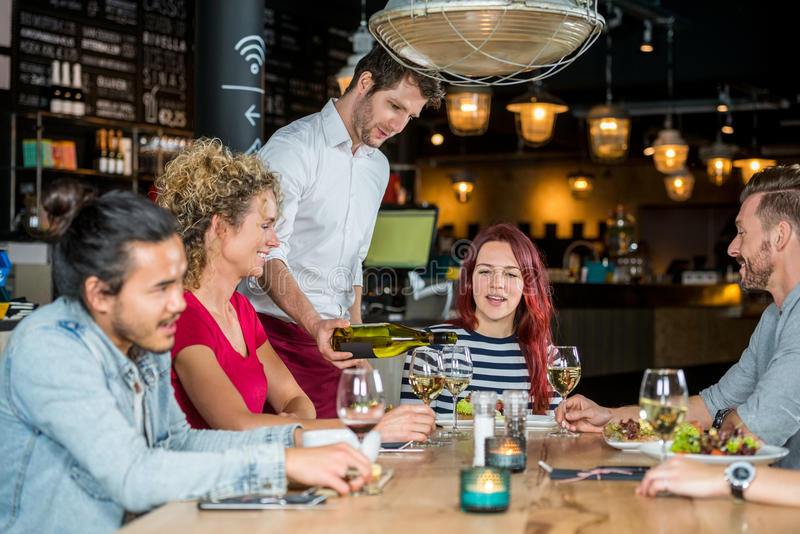 Waiter Serving Wine To Customers. Young waiter serving wine to customers at table in restaurant royalty free stock image