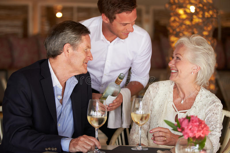 Waiter Serving Wine To Senior Couple In Restaurant. Waiter Serving Wine To Smiling Senior Couple In Restaurant stock images