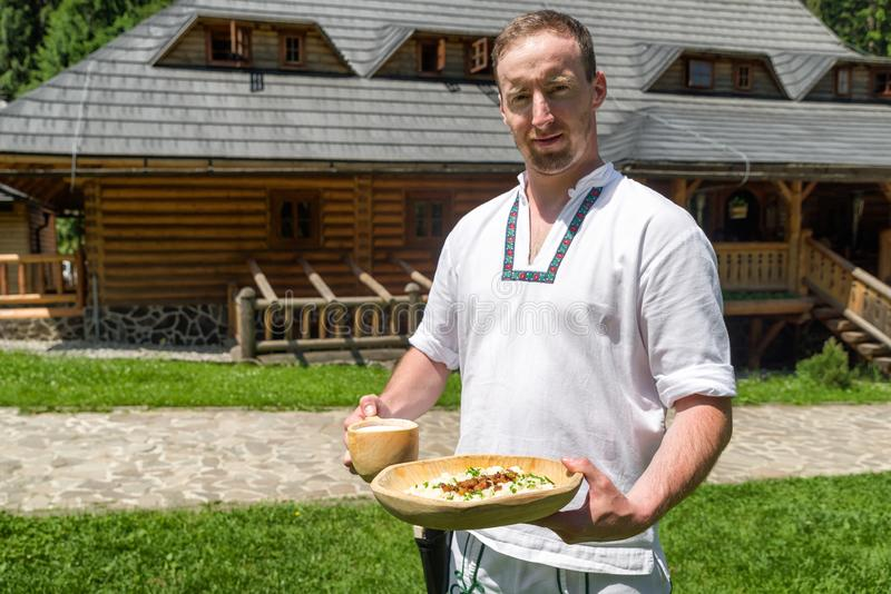 Bryndzove halusky - slovak national food. Waiter with Slovak potato dumplings with sheep cheese called Bryndzove halusky - national food of Slovakia royalty free stock images