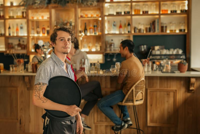 Waiter standing in a trendy bar ready to serve customers. Portrait of a young waiter holding a tray while standing in a trendy bar with customers in the stock photo
