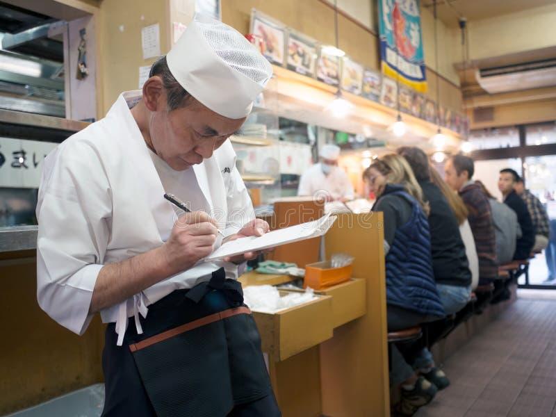 Waiter at sushi restaurant around tsukiji fish market. Tokyo, Japan - November 12, 2015: Waiter at sushi restaurant around Tsukiji fish market. Tsukiji is the stock image