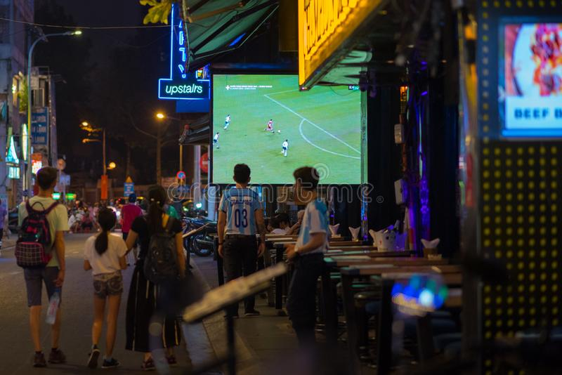 Waiter in T-shirt of Argentina blue-white design with writing `Champion` watches TV screen with football broadcast at Champion Bar royalty free stock photography