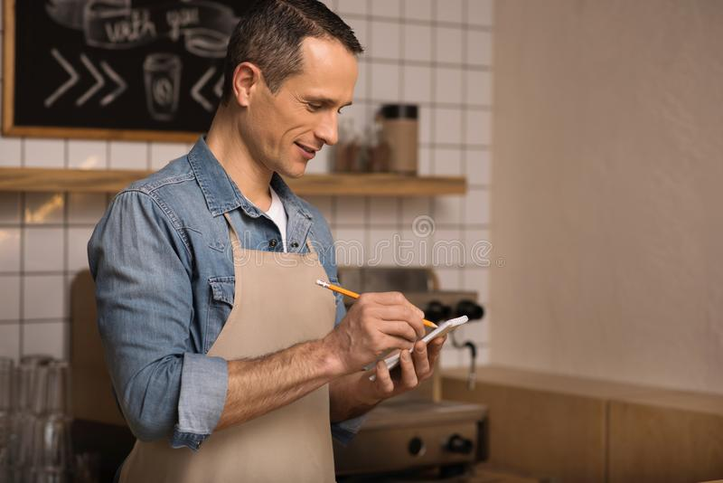 Waiter taking notes. Side view of waiter taking notes while working in cafe royalty free stock images