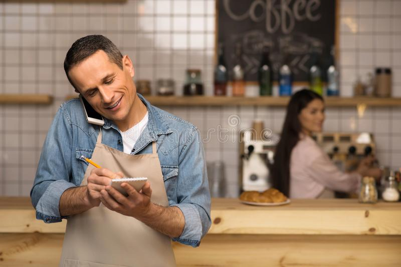 Waiter taking notes and talking on smartphone. With waitress on the background royalty free stock images