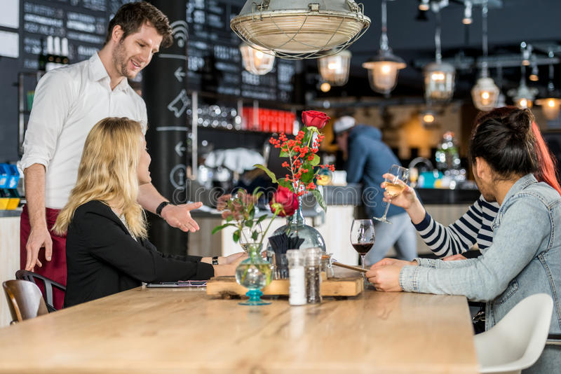 Waiter Taking Order From Customers In Cafe. Young waiter taking order from customers at table in cafe stock photography